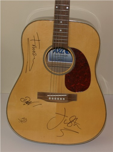 This is an acoustic guitar which has been hand signed in black pen by all four members of the rock