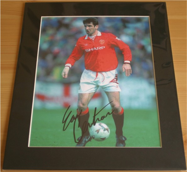 Eric Cantona has signed this superb photo in black pen. The item has been professionally mounted to