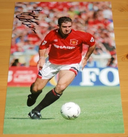 Old Trafford legend Eric Cantona has signed this superb photo in black pen.  COA - 0420000648