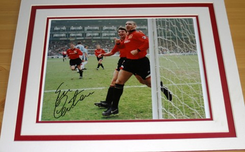 Old Trafford legend Eric Cantona has signed this superb photo in black pen.  The photograph has