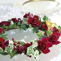 Deep red roses and ivy make up this delightful decoration adorned with a golden butterfly