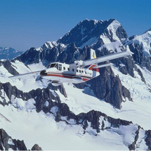 Soar over a snowy wonderland filled with towering icy peaks, azure blue lakes and sparkling glaciers